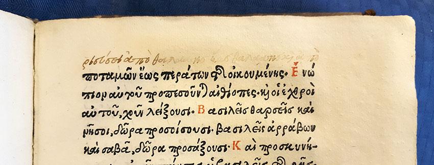 Foto av övre delen av en boksida tryckt med grekiska bokstäver. Över översta raden finns en tillagd handskriven rad på grekiska.