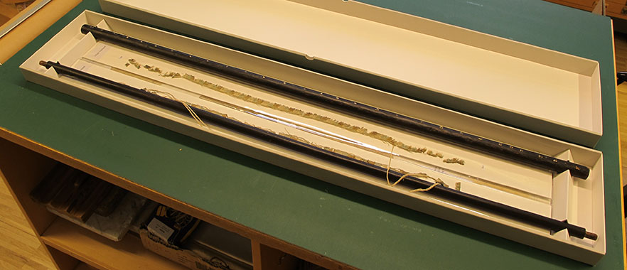 en öppen, långsmal låda där man ser träribbor och textilfragment ligga fixerade