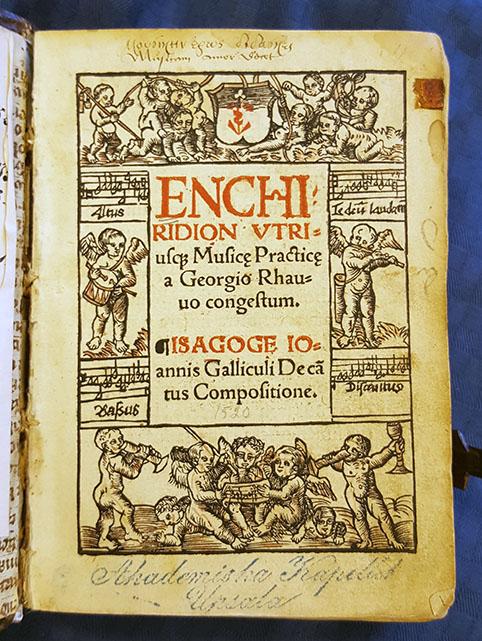 titelbladet till Enchiridion, med träsnitt av musicerande småänglar
