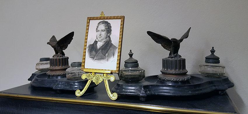 geijers tryckta porträtt i guldram stående överst på en hylla mellan bläckhorn och pennhållare