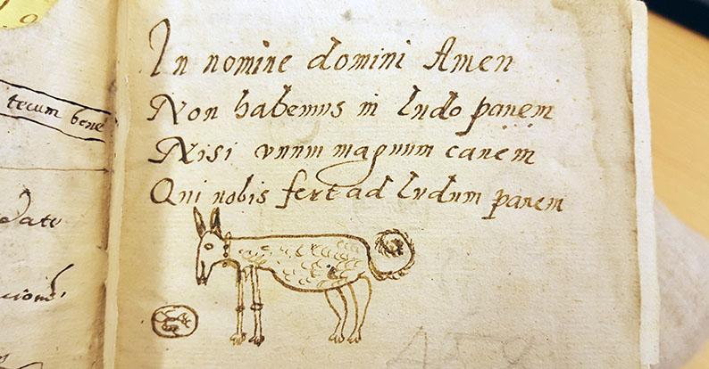 en handskriven latins vers under vilketn är tecknad en glad hund med en limpa under nosen