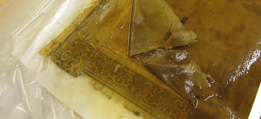 närbild på ett hörn där klotet avlägsnats från baksidan och hål och revor i pappret tydligt syns
