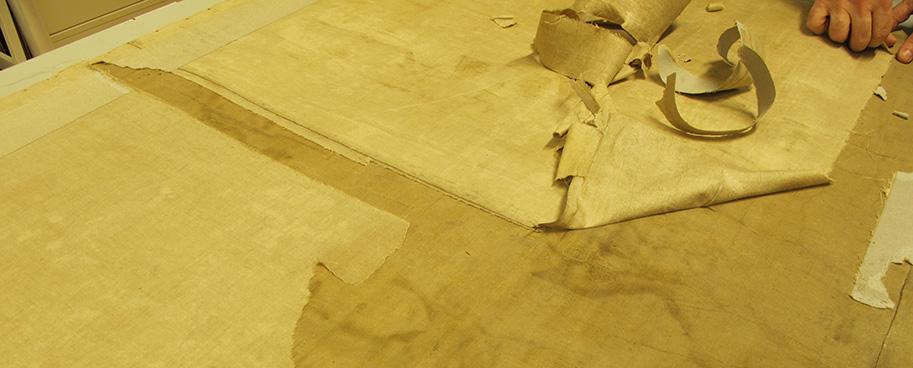 lösa textilfragment avlägsnas från kartans baksida