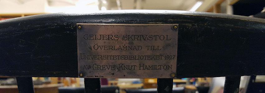 detalj av ryggstödet till en svart skrivbordsstol i trä med en metallplakett