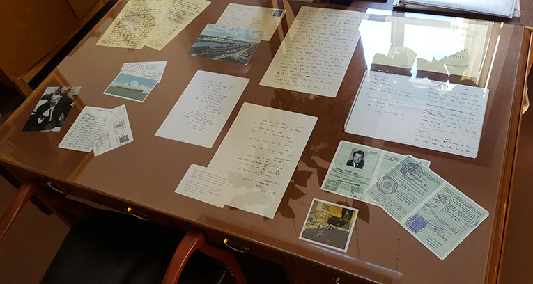 under en glasskiva på skrivbordet ligger foton och dokument med anknytning till Harry Martinson