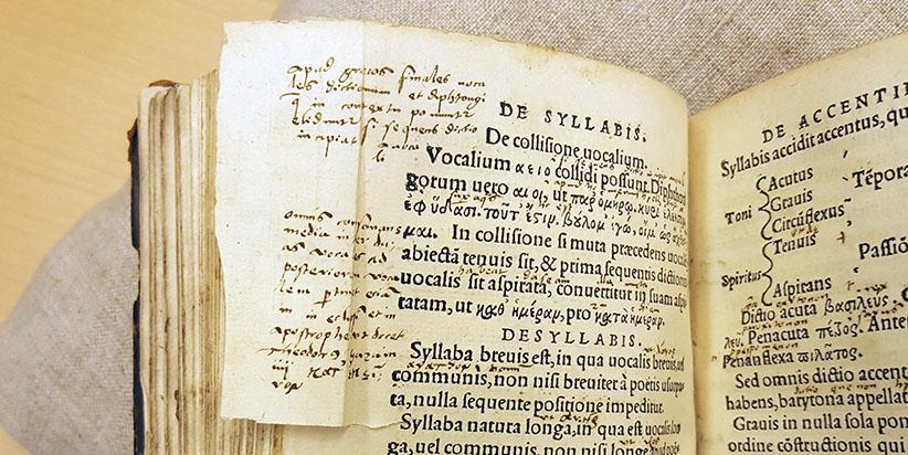 en sida med rikliga marginalanteckningar har vikts in för att inte texten ska försvinna då man skurit till snitten på boken