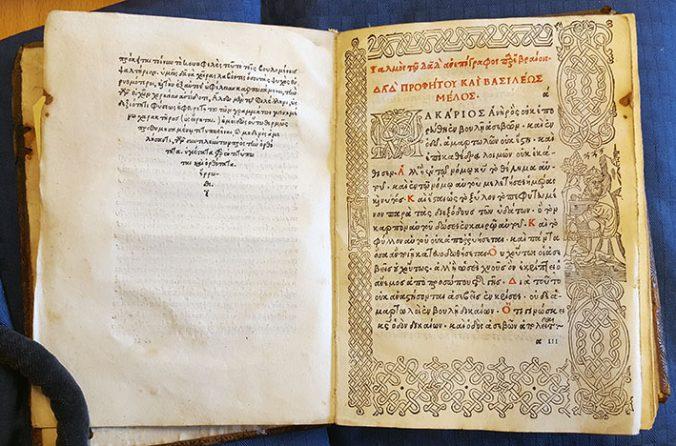 foto på ett uppslag i en bok tryckt med grekiska bokstäver i svart och rött. På högra sidan en ram i träsnitt runt texten.