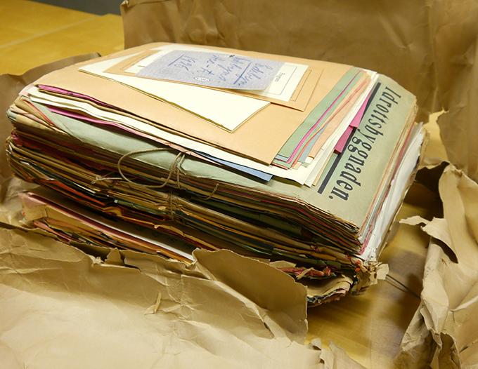 en bunt med tätt packade affischer ligger på ett bord, ett omslag av brunt papper har just rivits bort från den