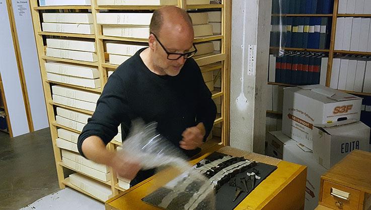 bokbindare Roger Johansson står vid ett bord där han jut lägger fram ett urval stämplar