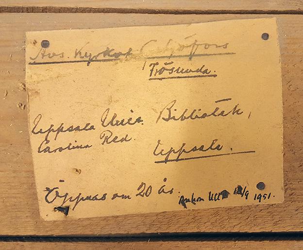 handskriven adresslapp adresserad till Uppsala universitetsbibliotek från 1951, klistrad på trälår