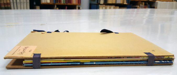 en liten bunt serietidningar ligger på ett bord, bunten är fast mellan två kartongark sammanknutna med bruna bomullsband