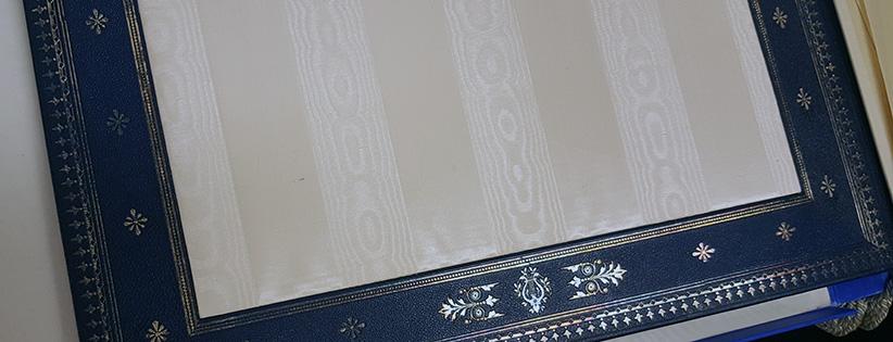 detalj av pärmens insida med vitt siden och tryck i guld och silver