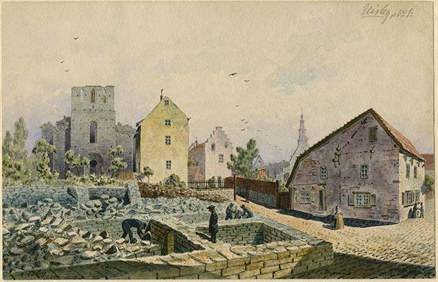 Färglagd teckning där man ser fyra män arbeta i en ruin i Visby, med en kyrkoruin och husgavlar i bakgrunden