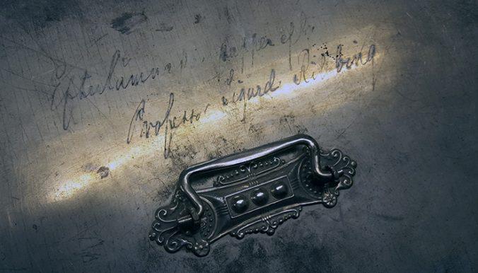närbild på handtaget på ett metallskrin, varöver det står: Efterlämnade papper av professor sigurd ribbing