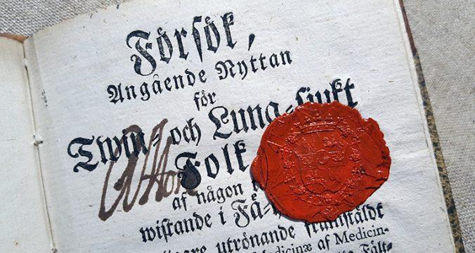 detalj av ett titelblad med rött lacksigill och en namnteckning