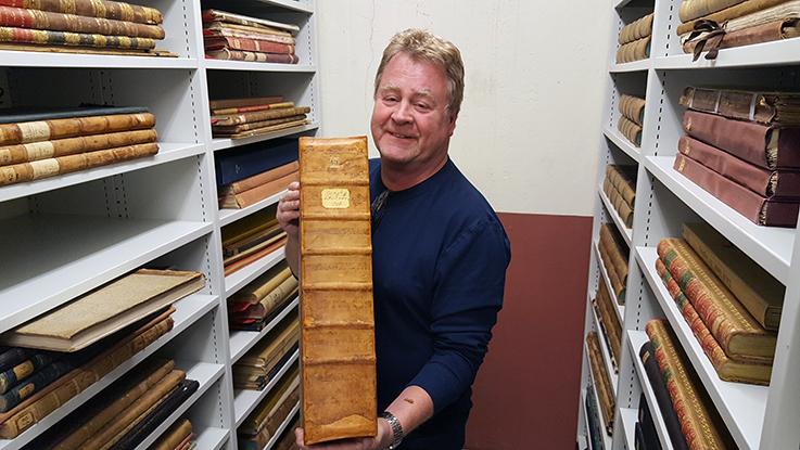 bokbindare Bosse Carlsson håller upp en stor bok mellan bokhyllor fulla med stora liggande böcker