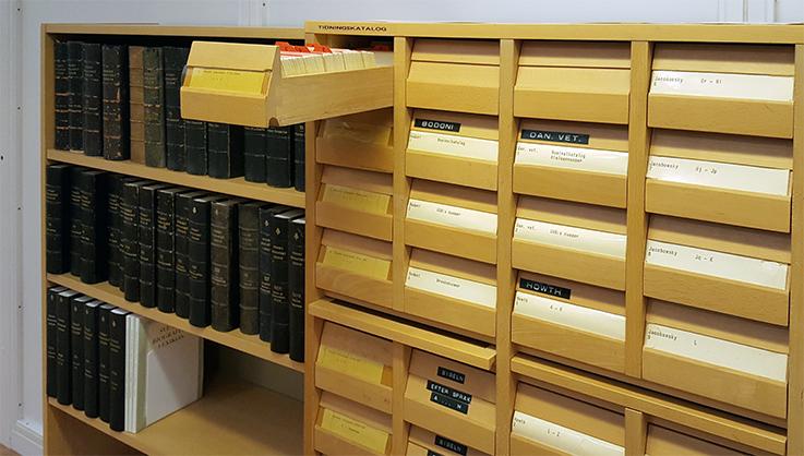 ett katalogskåp av trä med en låda utdragen