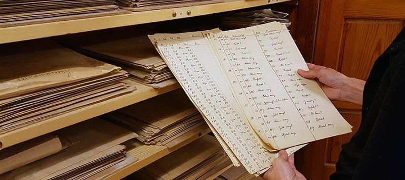 ett par händer håller upp ett par handskrivna listor som legat i skåpet