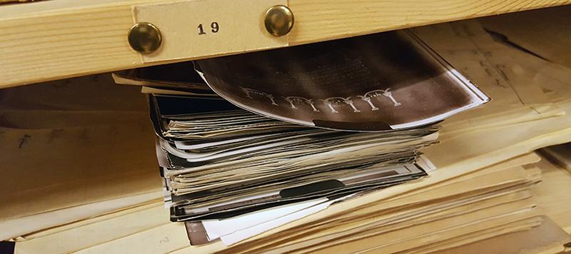 en hög med fotografier ligger på en trähylla i det öppna skåpet