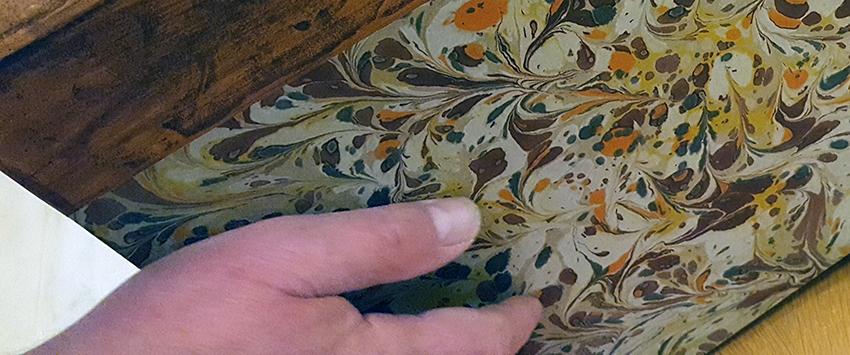 närbild på bokens pärmpapper, där Bosses hand syns till vänster i bild