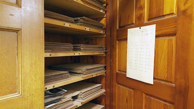 ett träskåp med en öppen skåpslucka, på hyllor ligger buntar med fotografier, kuvert och lösa papper