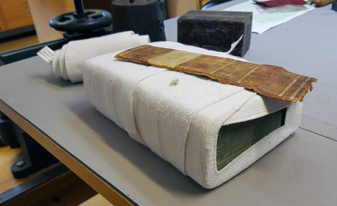 foto av en bok inlindad i vita bandage, ovanpå ligger en lös rygg