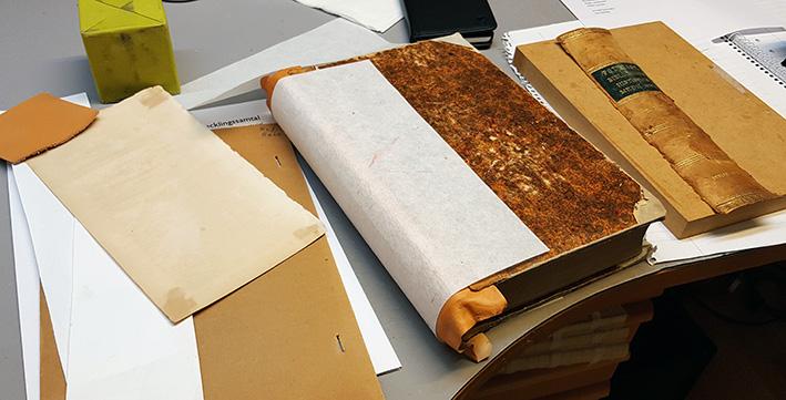 en bok under pågående lagning, där en ny rygg håller på att torka
