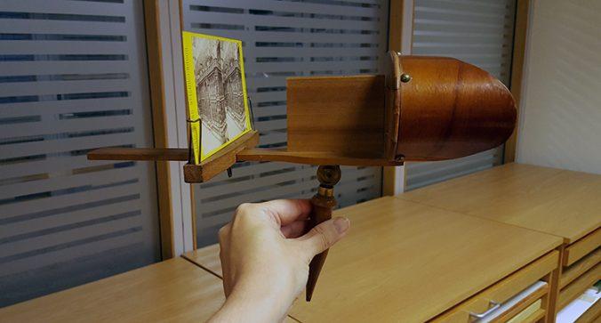 en nhand håller upp ett stereoskop med en bild istoppad