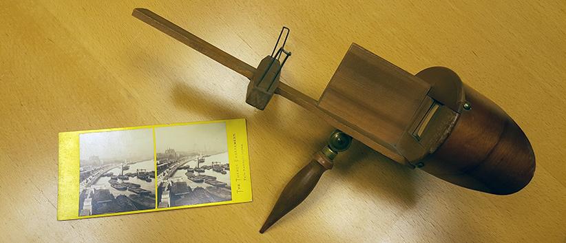stereoskopet ligger på ett träbord med ett stereofotografi över Themsen bredvid