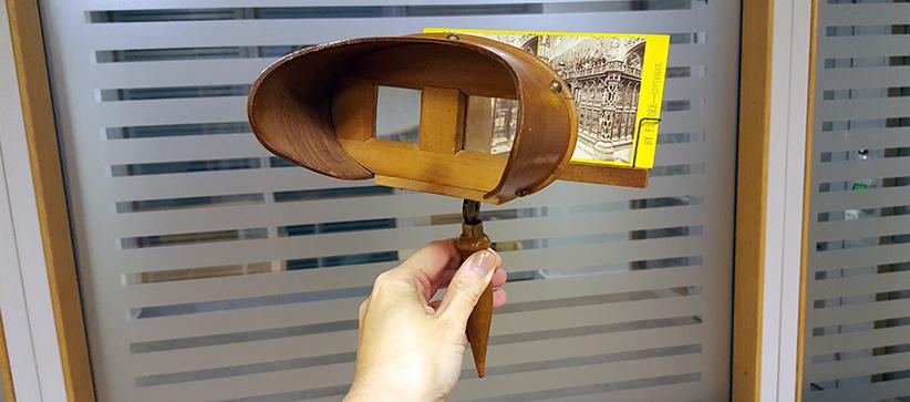 en hand håller stereoskopet i en vinkel, så att man kan ana bilden genom en av linserna