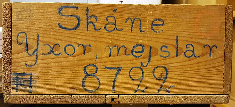 trälådans ena kant med texten Skåne, Yxor, mejslar 8722