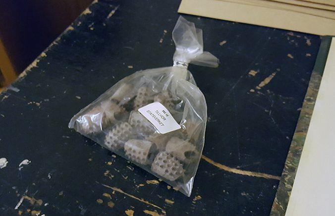 en liten plastpåse full av grå fingertutor i gummi med texten Tillhör Statsverket på en etikett