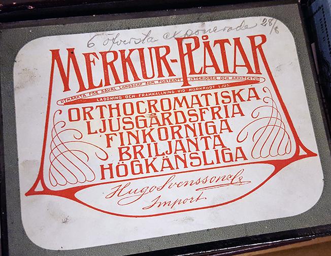 närbild på en etikett till en låda med glasnegativ, med namnet Merkur-plåtar i rött mot vit botten