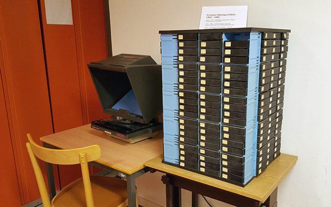 foto på en plasthylla på ett träbord, fylld av svarta mikrofilmskapslar