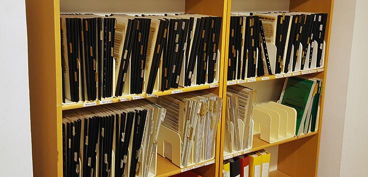 närbild på bokhylla där mappar med mikrofisches står på högkant.