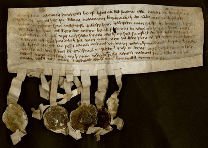 foto av ett medeltida pantbrev, med ett antal vaxsigill hängande från underkanten