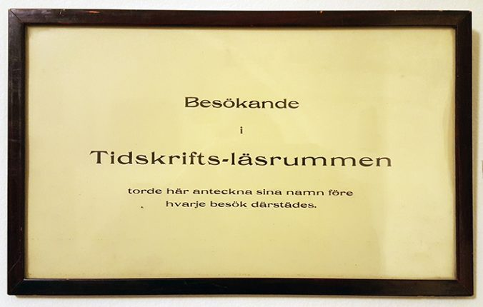 Skylt med texten Besökande i tidskriftsläsrummen torde här anteckna sina namn före besök därstädes