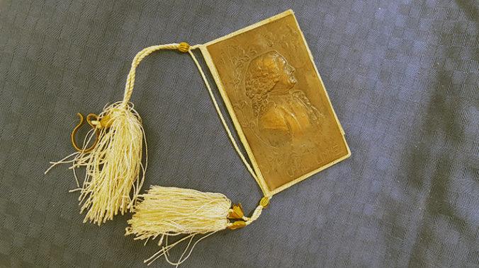 en liten bok med Linnés porträtt på framsidan, e snodd över ryggen med två avslutande, stora gula tofsar