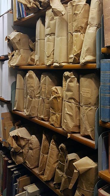 foto på en bokhylla full med bruna paket med pappsnören om