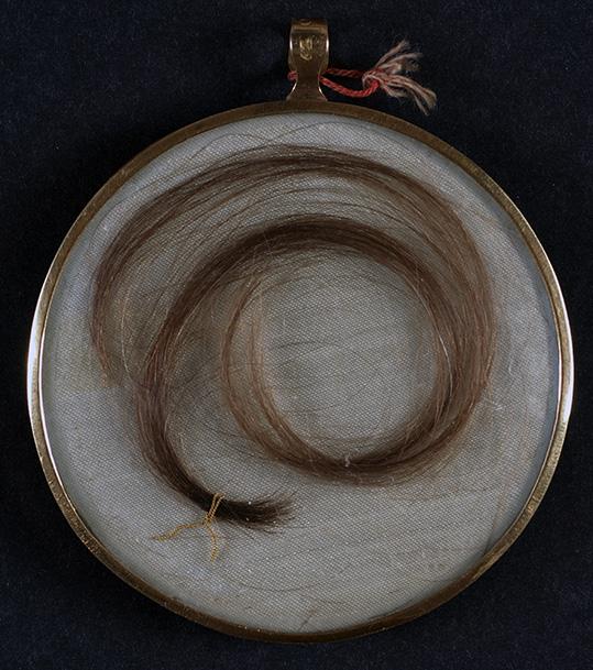 en hoprullad hårlock bakom glas i en medaljong