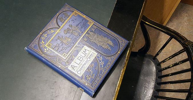 ett blått album med guldpressad dekor liggande på ett bord