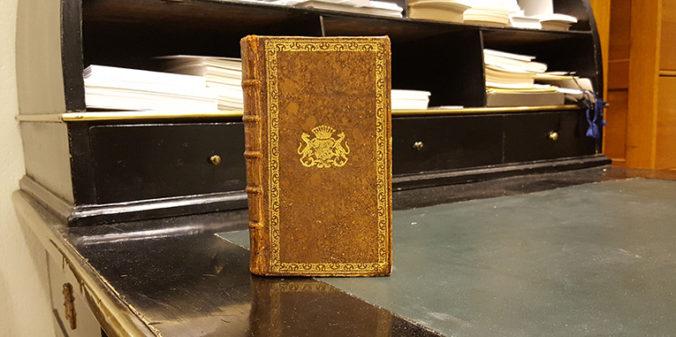 ett brent skinnband med ett pärmexlibris i guld stående på ett skrivbord