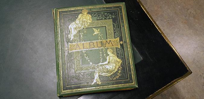 ett grönt album med guldtryckt dekor liggande på ett bord