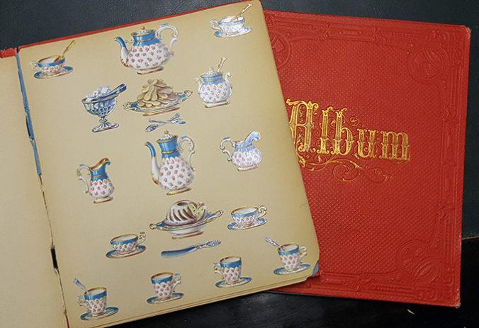 ett uppslaget album med bokmärken föreställande en servis liggande på ett rött album på ett svart bord