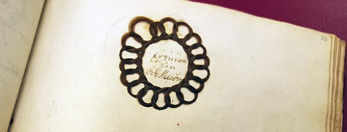 en hårkringla i form av en flätad krans runt en text
