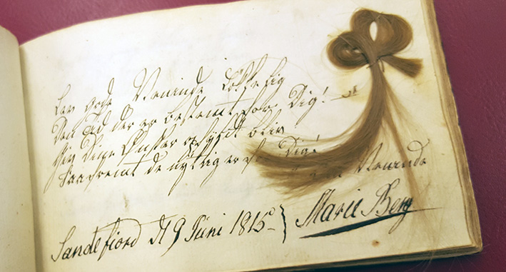 hårkringla med lång svans vid sidan av en text