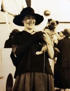 pearson på däcket till ett fartyg, glatt leende med en liten hund på armen