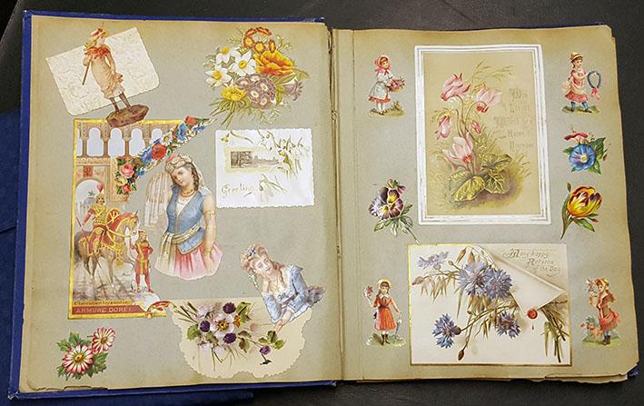 ett uppslag med fyra inklistrade vykort med blommotiv, med bokmärken med blommor och flickor klistrade runt om