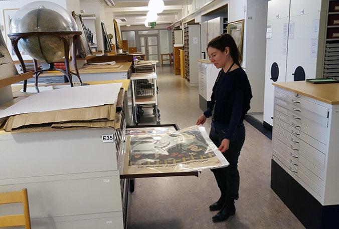 Foto av bibliotekare som drar ut en låda i ett kartskåp, vari det ligger en färgglad affisch