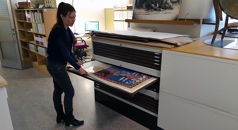 Bibliotekarie drar ur en låda ur ett kartskåp där en affisch skymtar fram